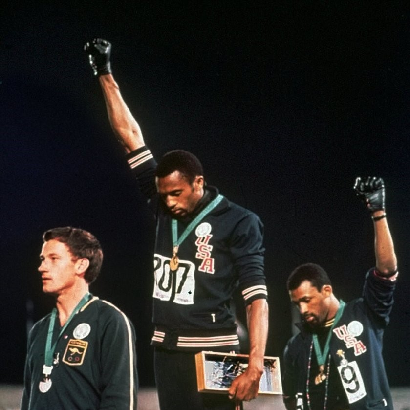 FILE- In this Oct. 16, 1968 file photo, U.S. athletes Tommie Smith, center, and John Carlos, right, stare extend their gloved hands skyward after Smith received the gold and Carlos the bronze for the 200 meter run at the Summer Olympic Games in Mexico City. Causes across the political spectrum have long used distinctive salutes to identify themselves. When Anders Behring Breivik, the far-right suspect in the massacre of 77 people in Norway, pulled his right hand to his chest and then thrust his arm out with a clenched fist after an Oslo courtroom guard removed his handcuffs on Monday, April 16, 2012; it was hardly the first time such a salute has been flashed (AP Photo/File)